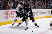 David Booth of the Vancouver Canucks and Willie Mitchell of the Los Angeles Kings fight for posession of the puck at STAPLES Center on January 4 2014...