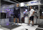 David Booth of the Vancouver Canucks practices his shot as Canucks skills coach Glenn Carnegie looks on before their NHL game against the Nashville...