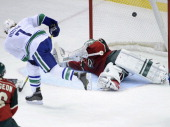 David Booth of the Vancouver Canucks shoots the puck over Josh Harding of the Minnesota Wild for a goal during the second period of the game on...