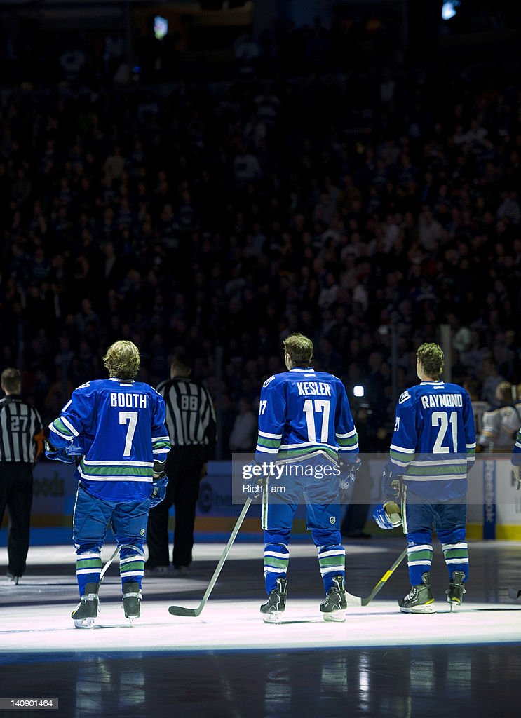David Booth Ryan Kesler and Mason Raymond of the Vancouver Canucks stand for the national anthems prior to NHL action against the Buffalo Sabres on...