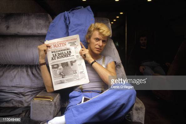 David Bowie holding up a copy of Le Matin De Paris newspaper during a plane journey May 1983