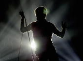 David Bowie in silhouette performs on the first night of his UK tour at the MEN Arena on November 17 2003 in Manchester England