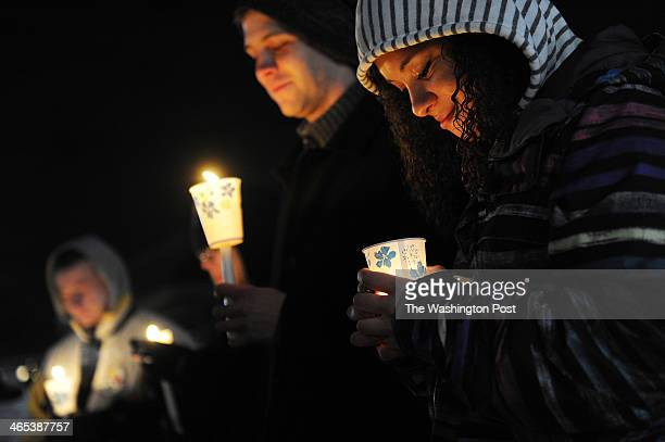 David Bowman left to right Ben Ganger and Nisa Pereira take part in a vigil on the waterfront of Lake Kittamaqundi for the shooting victims from the...
