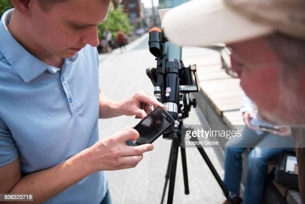 David Breeding tries to photograph the eclipse through Peter Girard right telescope during the partial solar eclipse in City Hall Plaza in Boston MA...