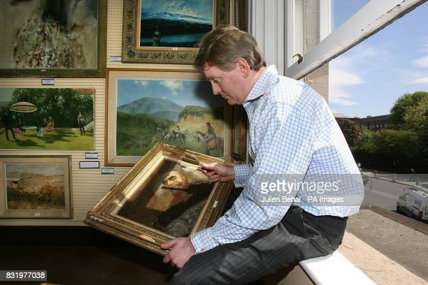 David Brittan Director of Adams and Sons Auction House examines a painting by artist Sarah Purser of Michael Davitt Father of the Irish Land League...