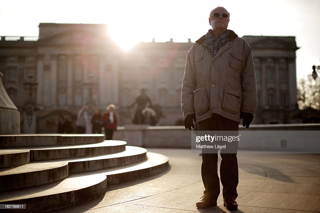 David Brooks from Newcastle enjoys the sunshine as he stands in front of Buckingham Palace next to the Queen Victoria Memorial on February 27, 2013 in London, England. The Met Office has predicted a cold period at Easter.