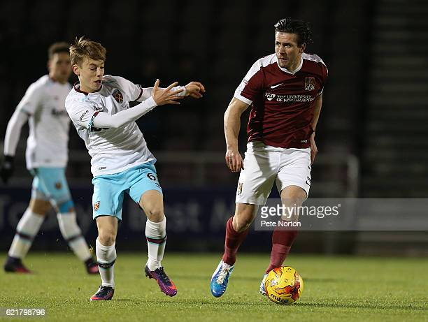David Buchanan of Northampton Town looks to play the ball watched by Dan Kemp of West Ham United U21 during the EFL Checkatrade Trophy match between...
