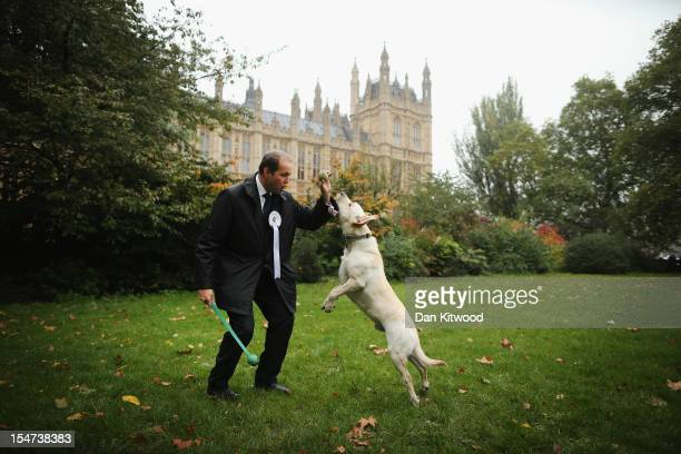 David Burrowes Conservative MP for Enfield Southgate stands in front of The Houses of Parliament with his dog Cholmeley a Labrador during the...
