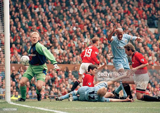 David Busst of Coventry City lies stricken with a broken leg after clashing with Brian McClair and Denis Irwin of Manchester United during the...