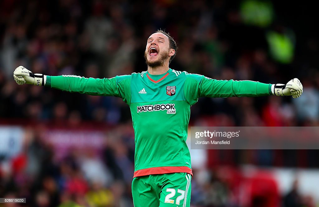 David Button of Brentford celebrates as Scott Hogan of Brentford scores their sides third goal during the Sky Bet Championship match between Brentford and Fulham at Griffin Park on April 30, 2016 in Brentford, England.