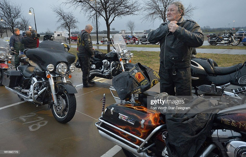 David Calhoun, right, Combat Veterans Motorcycle Association, of Weatherford, gets suited up before the funeral procession for Chris Kyle at Multi-Purpose Stadium, in Midlothian, Texas, Tuesday, February 12, 2013.