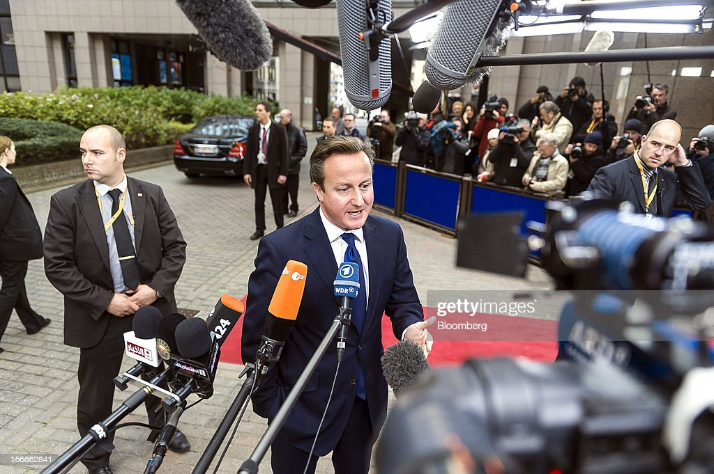 David Cameron, U.K. prime minister, center, speaks to the media as he arrives for the European Union (EU) leaders summit at the European Council headquarters in Brussels, Belgium, on Friday, Nov. 23, 2012. European Union leaders deadlocked over the bloc's next seven-year budget, adding to the quarrels between rich and poor countries that have stymied the response to the euro debt crisis. Photographer: Jock Fistick/Bloomberg via Getty Images