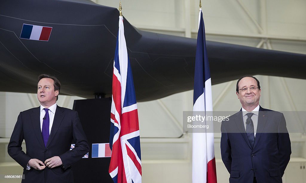 David Cameron, U.K. prime minister, left, adjusts his suit jacket as Francois Hollande, France's president, reacts following a joint news conference following a UK-France summit in Brize Norton, U.K., on Friday, Jan. 31, 2014. Hollande and David Cameron met at an airbase near Oxford today to push forward industrial accords on drones, missiles and mine detectors. Photographer: Simon Dawson/Bloomberg via Getty Images