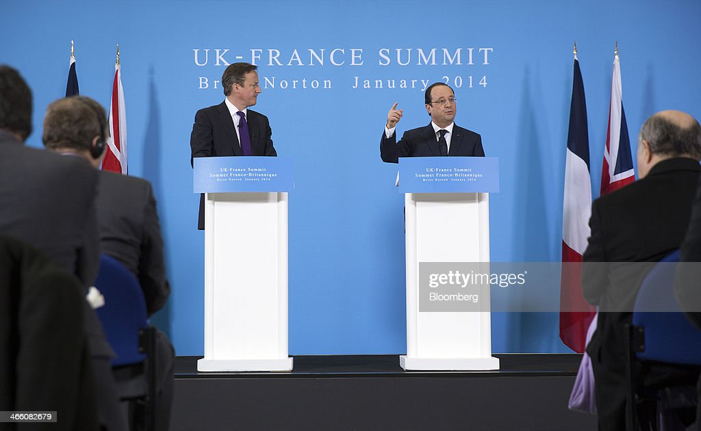 David Cameron, U.K. prime minister, left, listens as Francois Hollande, France's president, speaks during a joint news conference following a UK-France summit in Brize Norton, U.K., on Friday, Jan. 31, 2014. Hollande and David Cameron met at an airbase near Oxford today to push forward industrial accords on drones, missiles and mine detectors. Photographer: Simon Dawson/Bloomberg via Getty Images