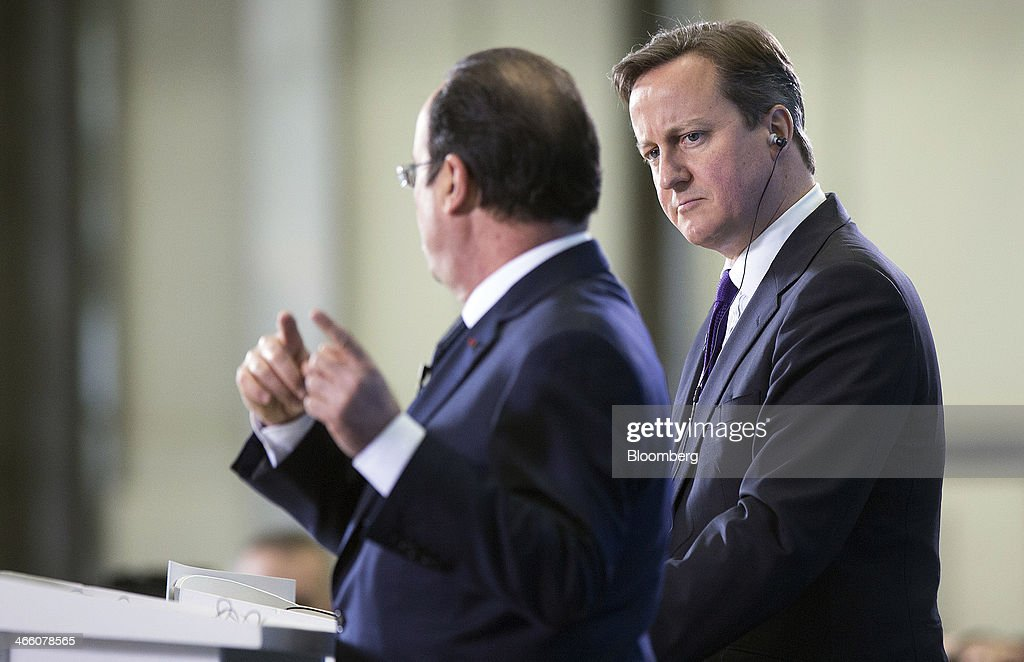 David Cameron, U.K. prime minister, right, listens as Francois Hollande, France's president, speaks during a joint news conference following a UK-France summit in Brize Norton, U.K., on Friday, Jan. 31, 2014. Hollande and David Cameron met at an airbase near Oxford today to push forward industrial accords on drones, missiles and mine detectors. Photographer: Simon Dawson/Bloomberg via Getty Images
