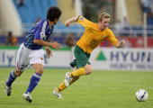 David Carney of Australia gets to the ball ahead of Akira Kaji during the AFC Asian Cup 2007 Quarter Final between Japan and the Australian Socceroos...