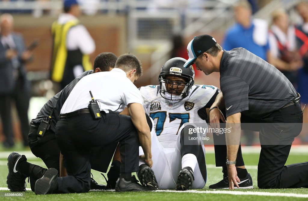 David Carter #77 of the Jacksonville Jaguars is attended to by the medical staff during the fourth quarter of the preseason game against the Detroit Lions at Ford Field on August 22, 2014 in Detroit, Michigan. The Lions defeated the Jaguars 13-12.