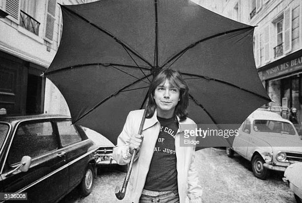 David Cassidy American pop singer and star of the television programme 'The Partridge Family' walking down a road in Paris with an umbrella 30th...