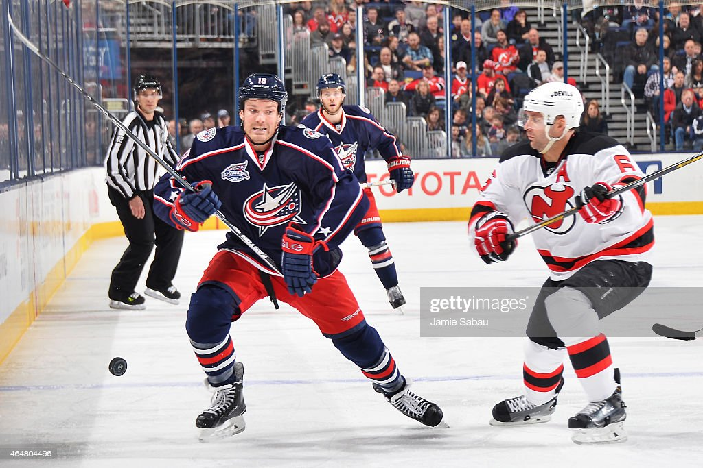 David Clarkson of the Columbus Blue Jackets attempts to avoid being checked by Andy Greene of the New Jersey Devils after passing the puck away...