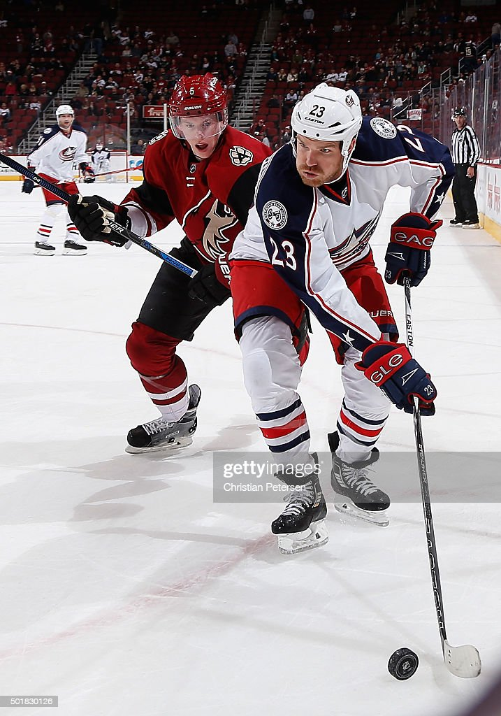 David Clarkson of the Columbus Blue Jackets looks to center the puck ahead of Connor Murphy of the Arizona Coyotes during the third period of the NHL...