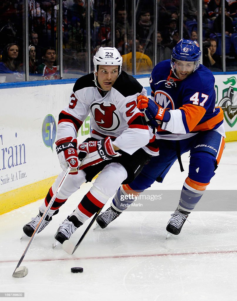 David Clarkson #23 of the New Jersey Devils and Andrew MacDonald #47 of the New York Islanders pursue a loose puck during the Islanders home opener at the Nassau Coliseum on January 19, 2013 in Uniondale, New York.