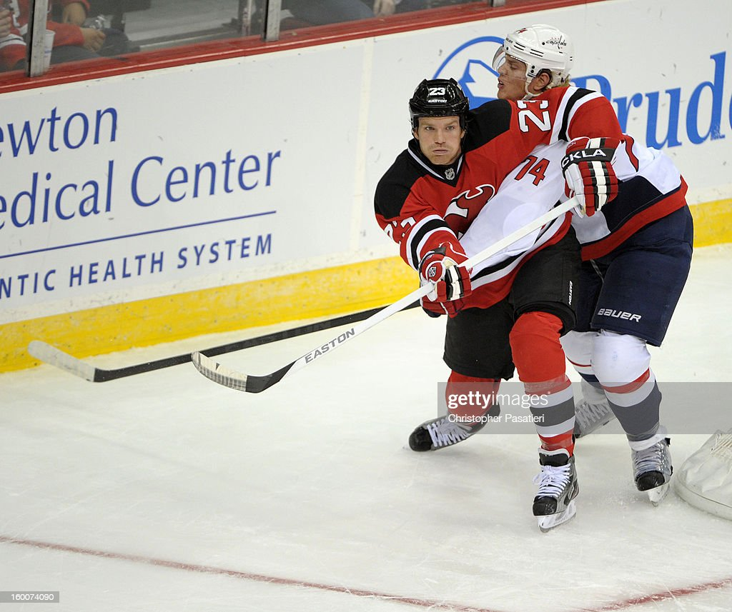 David Clarkson #23 of the New Jersey Devils gets tangled up with John Carlson #74 of the Washington Capitals during the game on January 25, 2013 at the Prudential Center in Newark, New Jersey.