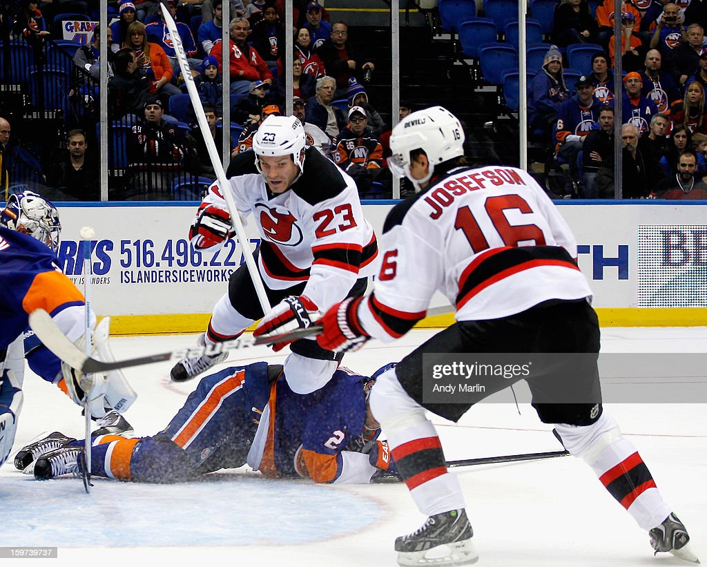 David Clarkson #23 of the New Jersey Devils goes flying over a prone <a gi-track='captionPersonalityLinkClicked' href=/galleries/search?phrase=Mark+Streit&family=editorial&specificpeople=636976 ng-click='$event.stopPropagation()'>Mark Streit</a> #2 of the New York Islanders during the Islanders home opener at the Nassau Coliseum on January 19, 2013 in Uniondale, New York.