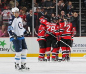 David Clarkson of the New Jersey Devils is congratulated by his teammates after scoring a secondperiod goal as Nik Antropov of the Winnipeg Jets...