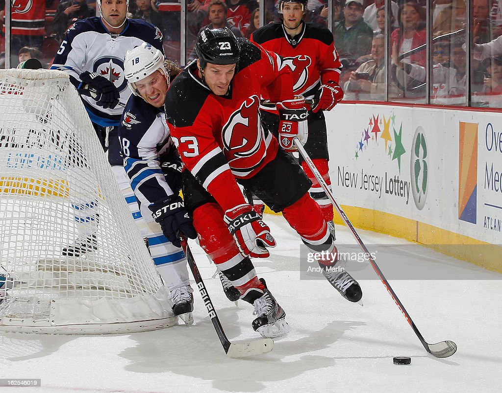 David Clarkson #23 of the New Jersey Devils plays the puck while being defended by <a gi-track='captionPersonalityLinkClicked' href=/galleries/search?phrase=Bryan+Little&family=editorial&specificpeople=540533 ng-click='$event.stopPropagation()'>Bryan Little</a> #18 of the Winnipeg Jets during the game at the Prudential Center on February 24, 2013 in Newark, New Jersey.