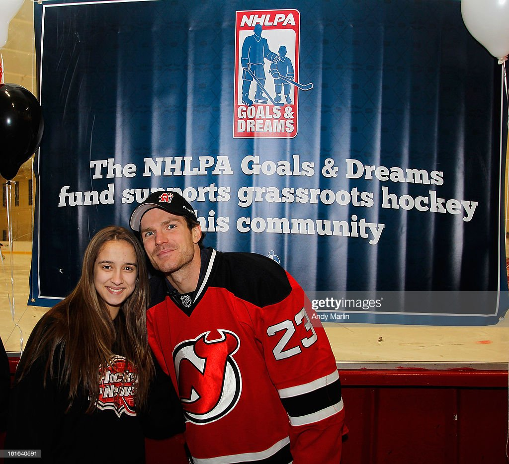 David Clarkson of the New Jersey Devils poses for a photo with a young girl during Hockey in Newark instructional clinic during on February 13, 2013 in Newark, New Jersey.