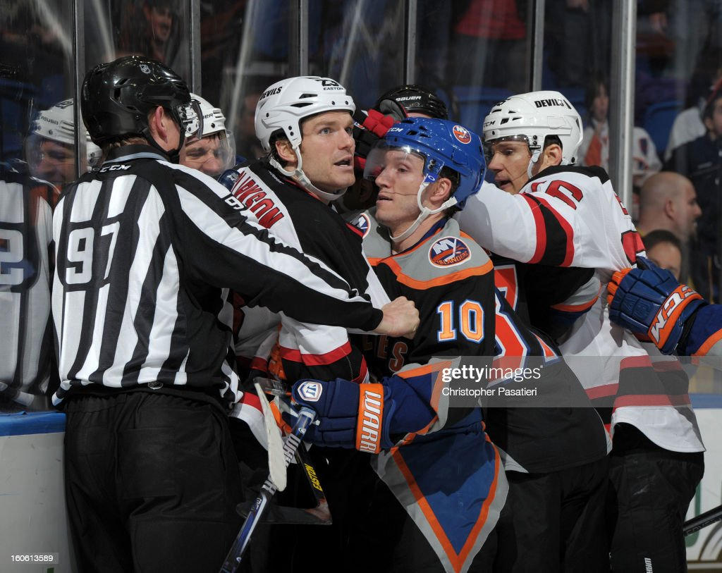 David Clarkson #23 of the New Jersey Devils scuffles with Keith Aucoin #10 of the New York Islanders during the game on February 3, 2013 at Nassau Veterans Memorial Coliseum in Uniondale, New York.