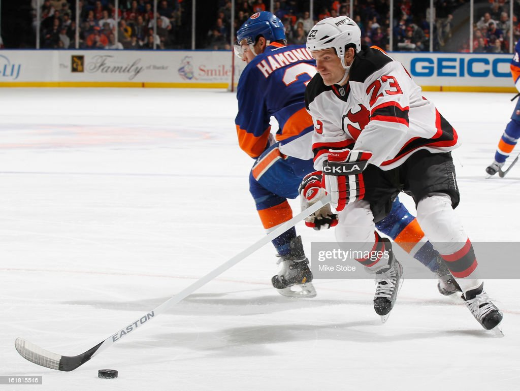 David Clarkson #23 of the New Jersey Devils skates around Travis Hamonic #3 of the New York Islanders at Nassau Veterans Memorial Coliseum on February 16, 2013 in Uniondale, New York.