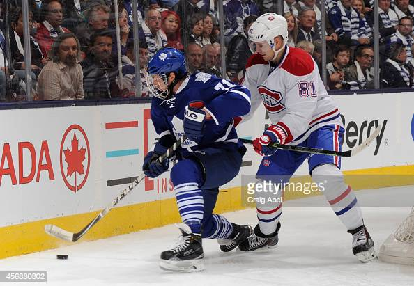 David Clarkson of the Toronto Maple Leafs battles for the puck with Lars Eller of the Montreal Canadiens during NHL season opener game action on...