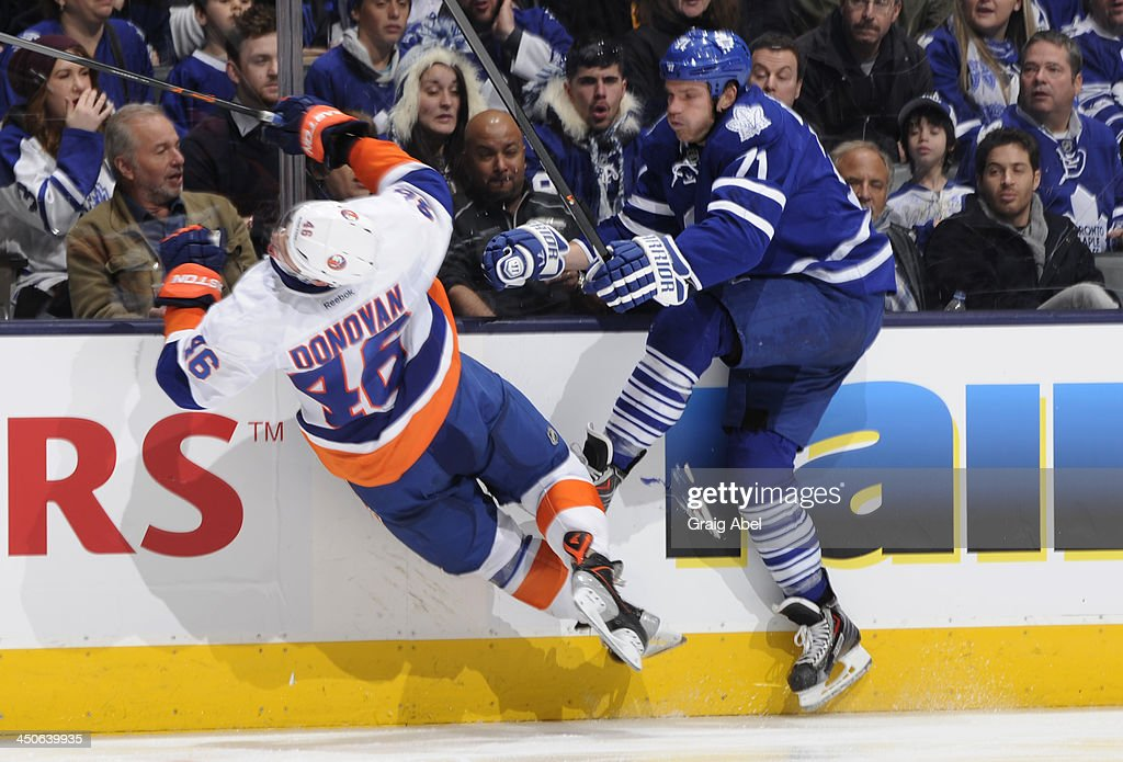 David Clarkson #71 of the Toronto Maple Leafs checks Matt Donovan #46 of the New York Islanders during NHL game action November 19, 2013 at the Air Canada Centre in Toronto, Ontario, Canada.