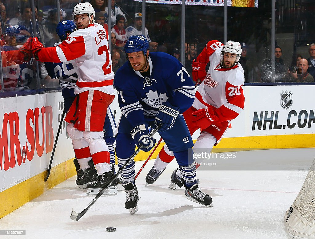 David Clarkson #71 of the Toronto Maple Leafs gets away from Drew Miller #20 and <a gi-track='captionPersonalityLinkClicked' href=/galleries/search?phrase=David+Legwand&family=editorial&specificpeople=202553 ng-click='$event.stopPropagation()'>David Legwand</a> #17 of the Detroit Red Wings during NHL action at the Air Canada Centre March 29, 2014 in Toronto, Ontario, Canada.