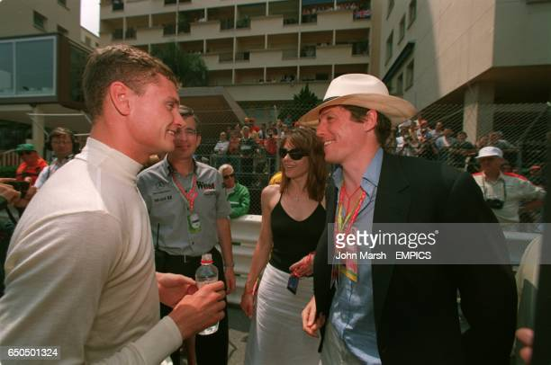 David Coulthard chats to Liz Hurley and Hugh Grant before the race