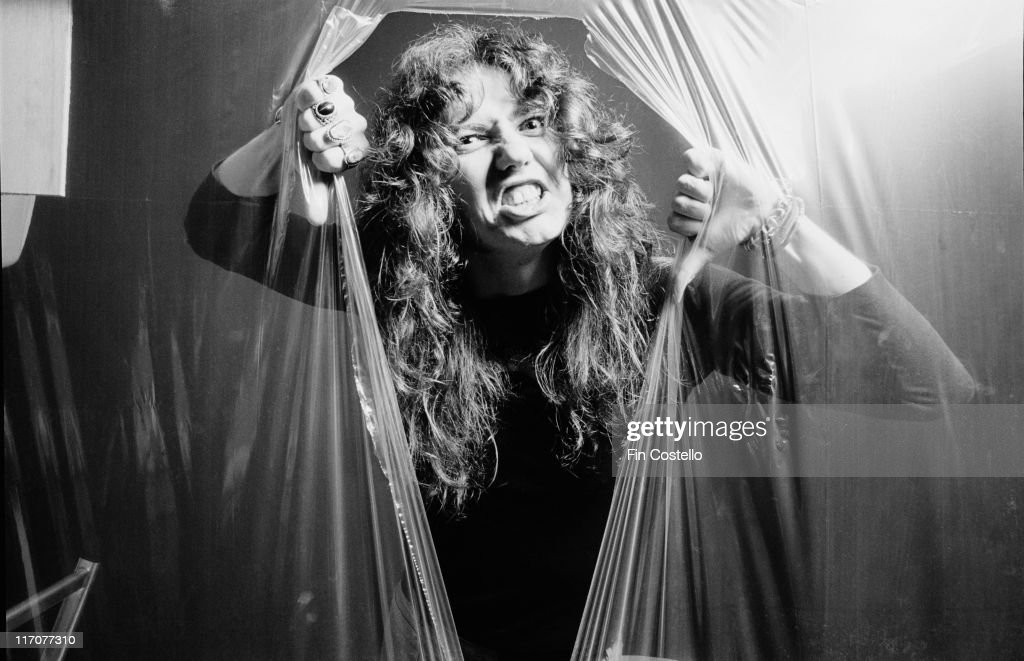 David Coverdale, singer with British rock band Whitesnake, grimacing as he tears his way out through a sheet of clear plastic in a studio portrait, 1978.