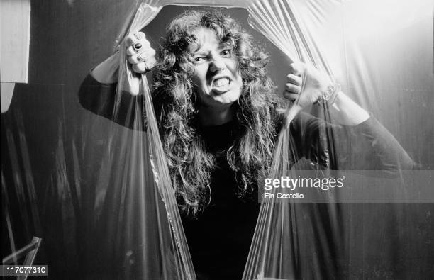 David Coverdale singer with British rock band Whitesnake grimacing as he tears his way out through a sheet of clear plastic in a studio portrait 1978