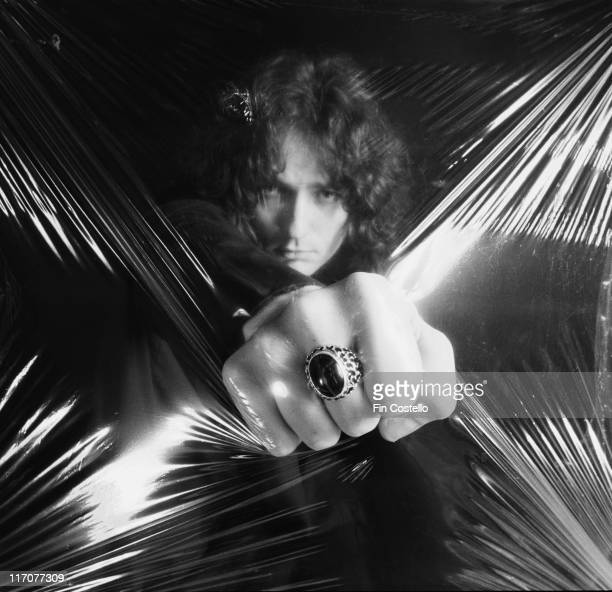 David Coverdale singer with British rock band Whitesnake punching into a sheet of clear plastic in a studio portrait 1978