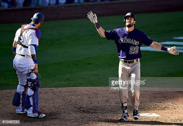 David Dahl of the Colorado Rockies celebrates his solo homerun in front of Yasmani Grandal of the Los Angeles Dodgers to take a 32 lead during the...