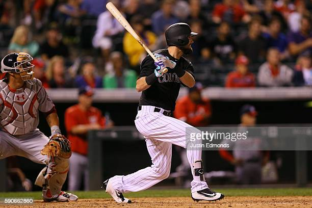 David Dahl of the Colorado Rockies watches his pinch hit two RBI double as catcher Wilson Ramos of the Washington Nationals looks on during the...