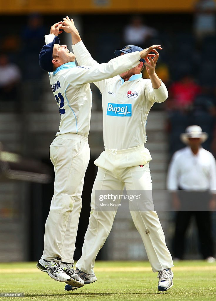 David Dawson (L) and Peter Neville of the Blues celebrate the wicket of Michael Hussey of the Warriors during day one of the Sheffield Shield match between the New South Wales Blues and the Western Australia Warriors at Blacktown International Sportspark on January 24, 2013 in Sydney, Australia.