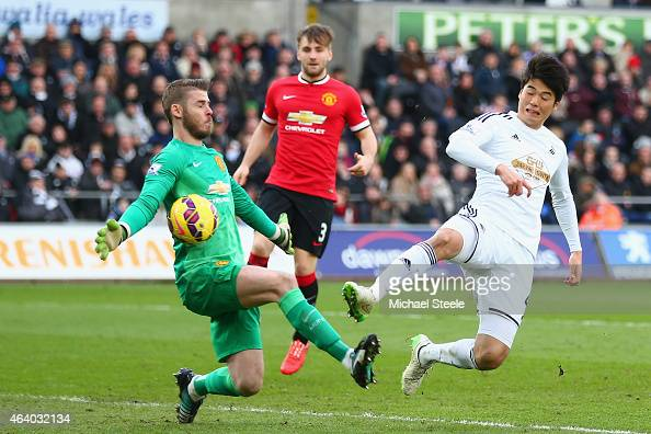 David De Gea of Manchester United makes a save from Ki SungYueng of Swansea City during the Barclays Premier League match between Swansea City and...