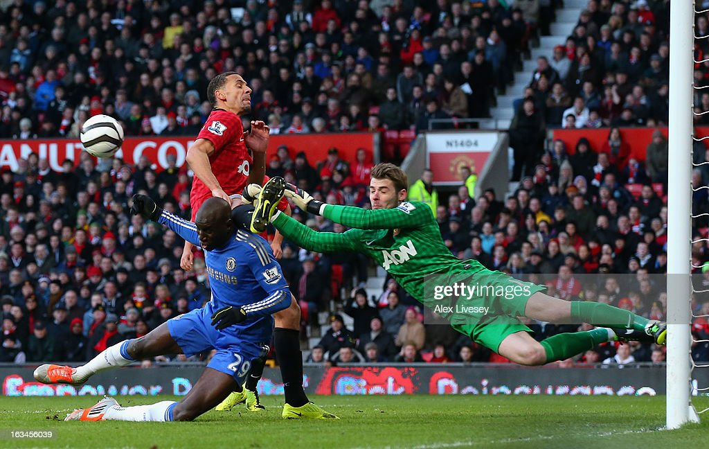 David De Gea of Manchester United punches clear under pressure from Demba Ba of Chelsea during the FA Cup sponsored by Budweiser Sixth Round match between Manchester United and Chelsea at Old Trafford on March 10, 2013 in Manchester, England.