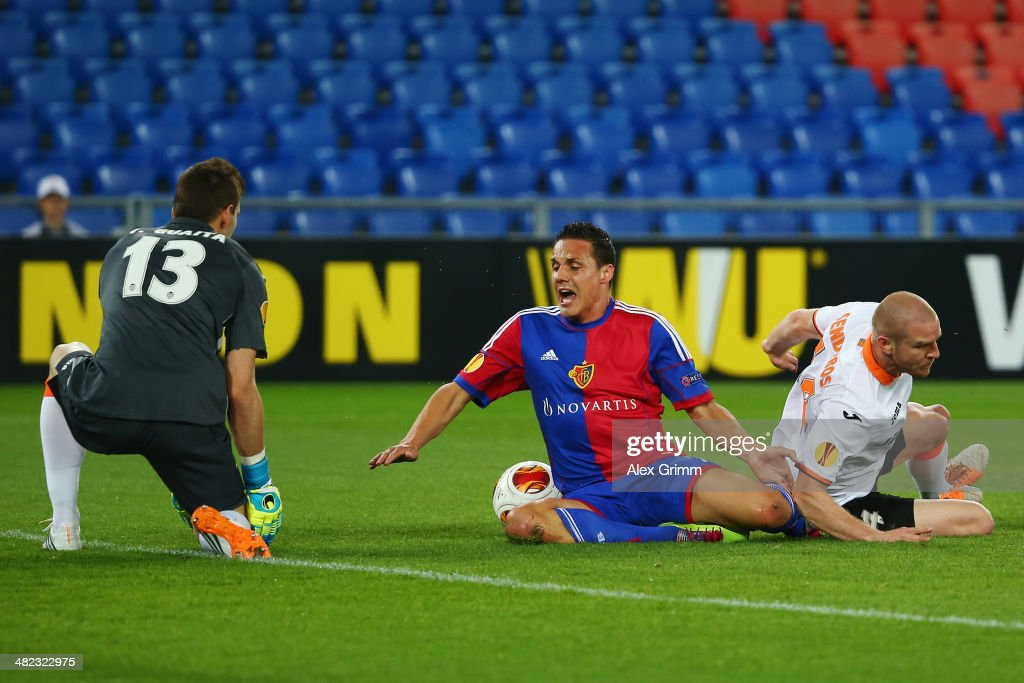 David Degen (C) of Basel is challenged in the penalty box by goalkeeper Vicente Guaita and <a gi-track='captionPersonalityLinkClicked' href=/galleries/search?phrase=Philippe+Senderos&family=editorial&specificpeople=221471 ng-click='$event.stopPropagation()'>Philippe Senderos</a> of Valencia during the UEFA Europa League Quarter Final first leg match between FC Basel 1893 and FC Valencia at St. Jakob-Park on April 3, 2014 in Basel, Switzerland.