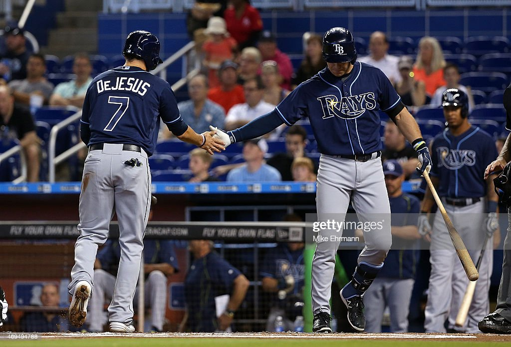 David DeJesus is congratulated by Evan Longoria of the Tampa Bay Rays after scoring during a game against the Miami Marlins at Marlins Park on April...