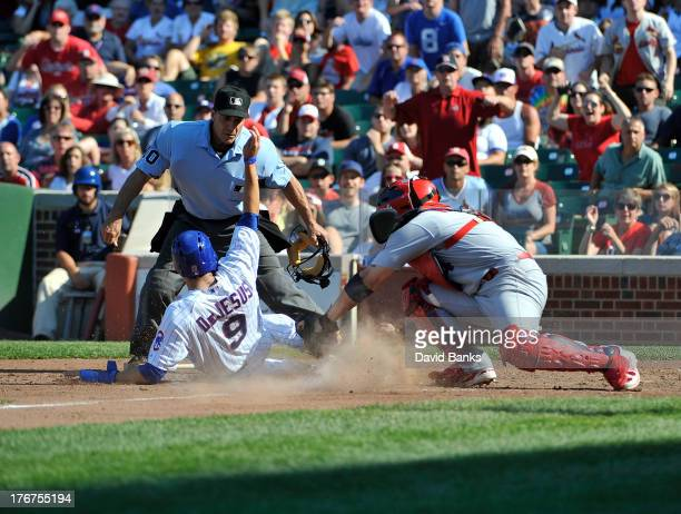 David DeJesus of the Chicago Cubs is tagged out at home by Yadier Molina of the St Louis Cardinals during the eighth inning on August 18 2013 at...