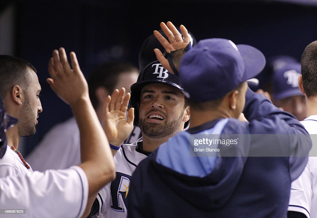 <a gi-track='captionPersonalityLinkClicked' href=/galleries/search?phrase=David+DeJesus&family=editorial&specificpeople=206765 ng-click='$event.stopPropagation()'>David DeJesus</a> (C) of the Tampa Bay Rays celebrates in the dugout after scoring off of James Loney's sacrifice fly during the fourth inning of a game against the Cleveland Indians on May 9, 2014 at Tropicana Field in St. Petersburg, Florida.