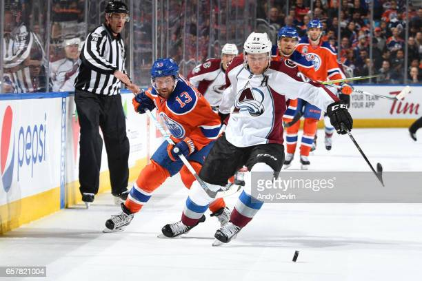 David Desharnais of the Edmonton Oilers battles for the puck against Nathan MacKinnon of the Colorado Avalanche on March 25 2017 at Rogers Place in...