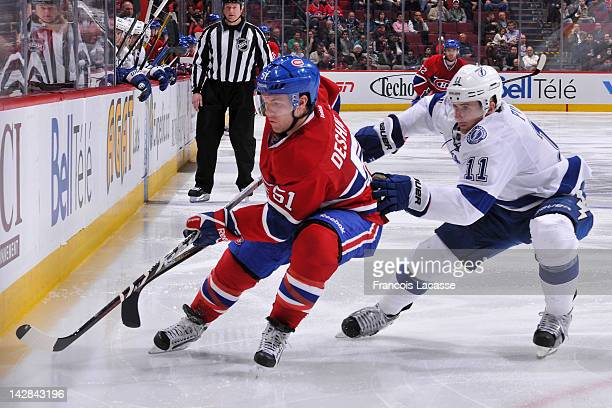 David Desharnais of the Montreal Canadiens and Tom Pyatt of the Tampa Bay Lightning skate towards a looose puck in the corner during the NHL game on...